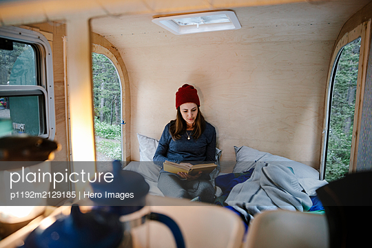 Woman relaxing, reading book on bed in camper van - p1192m2129185 by Hero Images