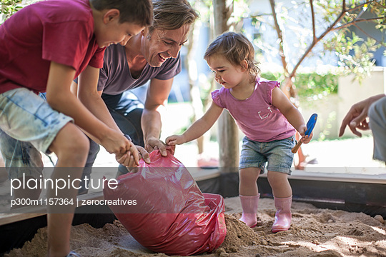 Family filling sand into sandpit - p300m1157364 by zerocreatives