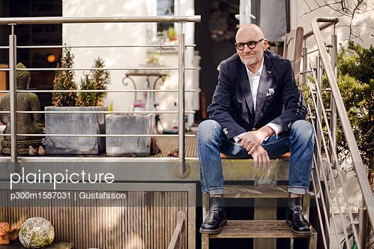 Senior man sitting on stairs of his patio - p300m1587031 von Gustafsson