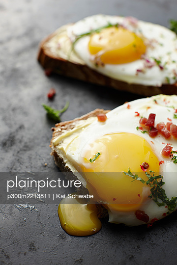 Fried eggs, chives, bacon and bread - p300m2213811 by Kai Schwabe
