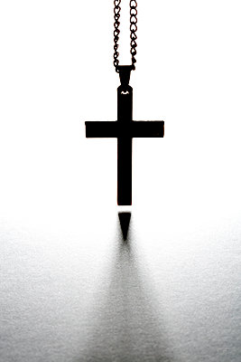 An old metal cross or crucifix hanging from a metal chain, a religious icon or symbol often used by the christian faith. - p1057m1572923 by Stephen Shepherd