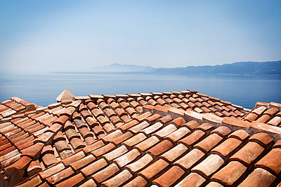 Roofs by sea against clear blue sky - p1166m1151231 by Cavan Images