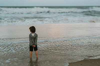 Rear view of boy standing in sea during sunset - p1166m2034797 by Cavan Images