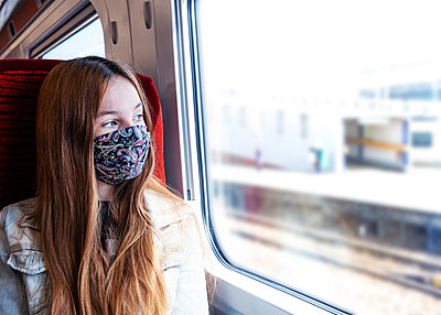 Young teenager looking concerned travelling on a train wearing a mask - p1166m2247965 by Cavan Images