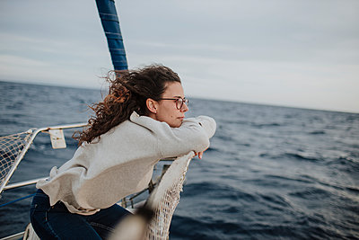 Thoughtful woman looking away while leaning on sailboat - p300m2276444 by Gala Martínez López