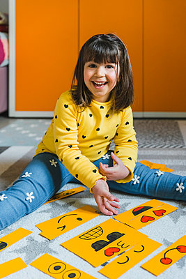 Excited girl playing with emoticons on floor at home - p300m2282406 by Giorgio Magini