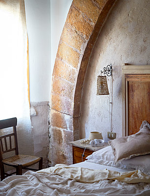 Unmade bed with stone arch and wooden chair, Sicily, Italy.  - p349m2167751 by Polly Wreford