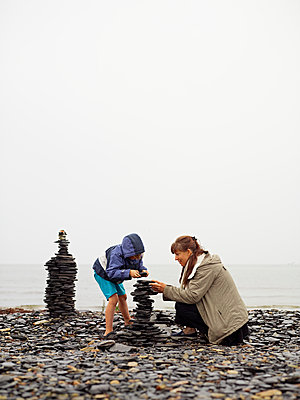 Sweden, Oland, Mother and daughter (4-5) building cairn on beach - p352m1061597f by Love Lannér