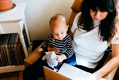 Mother using laptop with son on lap - p429m974589 by Kate Ballis