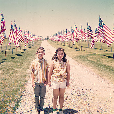 Caucasian brother and sister holding hands near American flags - p555m1444163 by PBNJ Productions