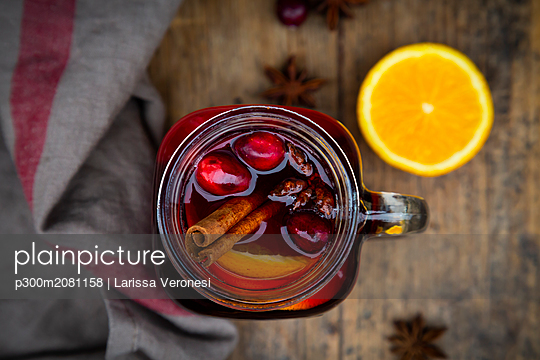 Glass of mulled wine with cranberries, cinnamon sticks, orange and star anise on dark wood, focus on foreground - p300m2081158 by Larissa Veronesi