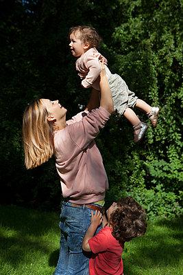 Familie tobt zusammen im Garten - p045m1488341 von Jasmin Sander