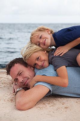 Die Söhne machen es sich auf Papas Rücken gemütlich - p045m2028271 von Jasmin Sander