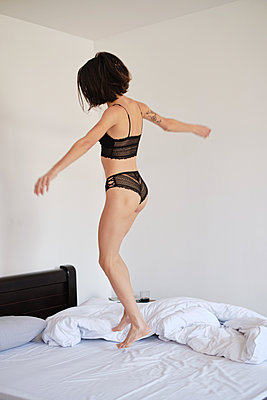 Young brunette woman jumping in her bed at morning - p1607m2183919 by zhushman
