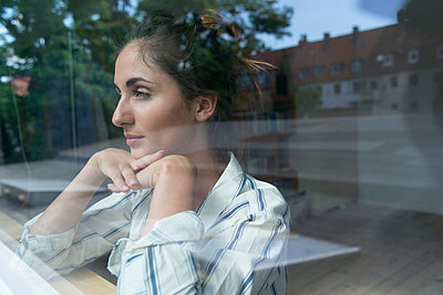 Young woman looking out of window - p427m1195218 by R. Mohr