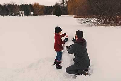 Father and daughter making snowman - p924m1230297 by Kymberlie Dozois Photography