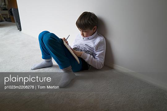 Boy home schooling on floor - p1023m2208278 by Tom Merton