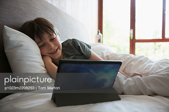 Smiling boy using digital tablet in bed - p1023m2208293 by Tom Merton