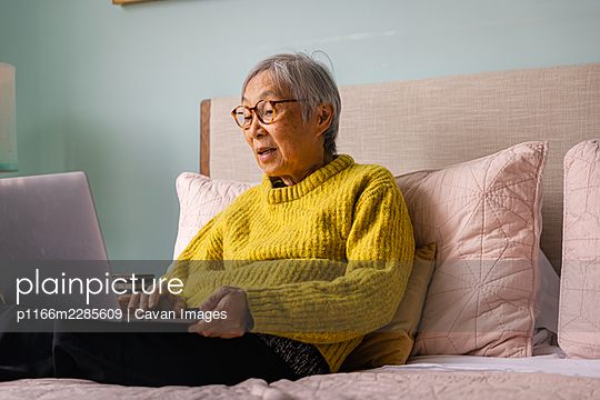 Senior asian woman using laptop while sitting in bedroom at home - p1166m2285609 by Cavan Images