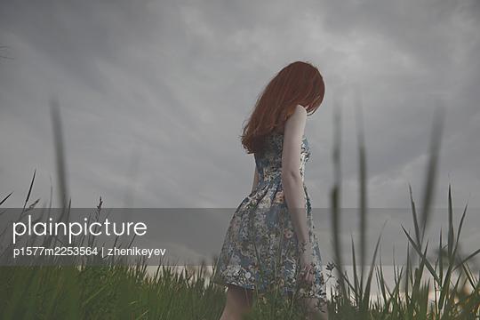 Redhead woman walking in the field - p1577m2253564 by zhenikeyev