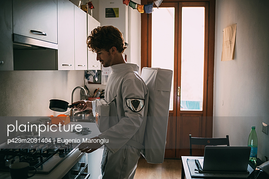 Astronaut cooking in kitchen - p429m2091404 by Eugenio Marongiu