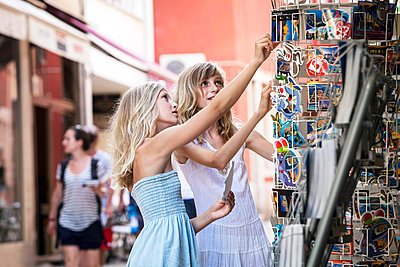 Two girls buying picture postcards together - p1026m874736f by Dario Secen