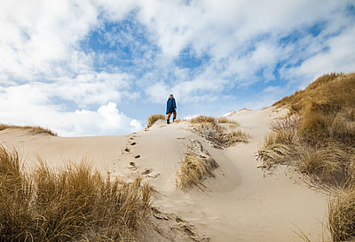 Woman walking up sand dunes in winter with blue sky and clouds - p1166m2261167 by Cavan Images