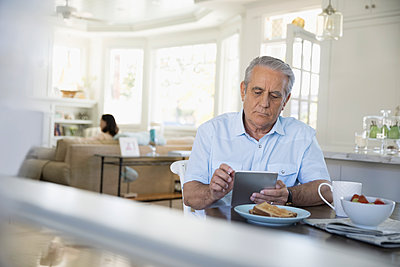 Senior man using digital tablet and eating breakfast in beach house - p1192m1418537 by Hero Images