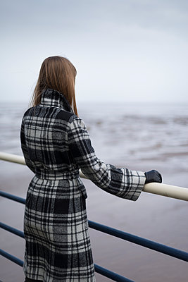 Woman looking out at sea from a pier at low tide. - p1433m1589975 by Wolf Kettler