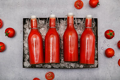 Row of four ice-cooled swing top bottles with homemade tomato juice - p300m1587738 by Retales Botijero