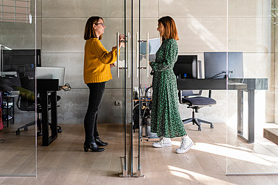 Female coworkers discussing while standing in cabin at office - p300m2265045 by Javier De La Torre Sebastian