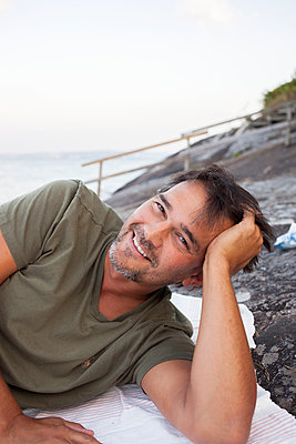 Smiling man relaxing on beach - p312m1472381 by Christina Strehlow