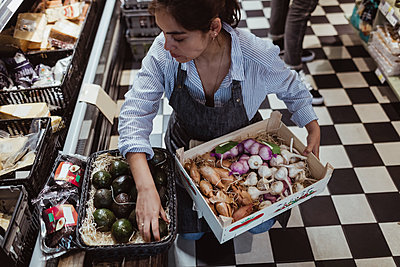 High angle view of sales woman arranging fruits and vegetables in box at deli store - p426m2270471 by Maskot