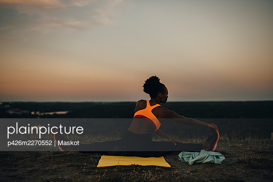 Rear view of female athlete doing yoga during sunset - p426m2270552 by Maskot