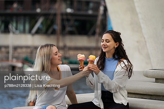 Two young women eating ice cream - p788m2128338 by Lisa Krechting