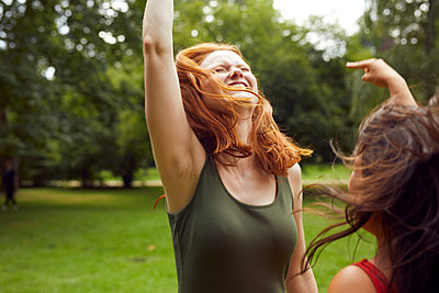 Two young women dancing together in a park - p1491m2176069 by Jessica Prautzsch