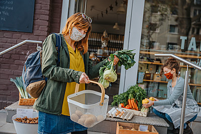 Costumer putting vegetables into basket at organic food store, Cologne, NRW, Germany - p300m2256155 von Mareen Fischinger