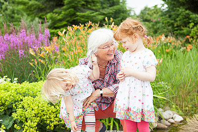 Grandmother playing with granddaughters - p505m1048196 by Iris Wolf