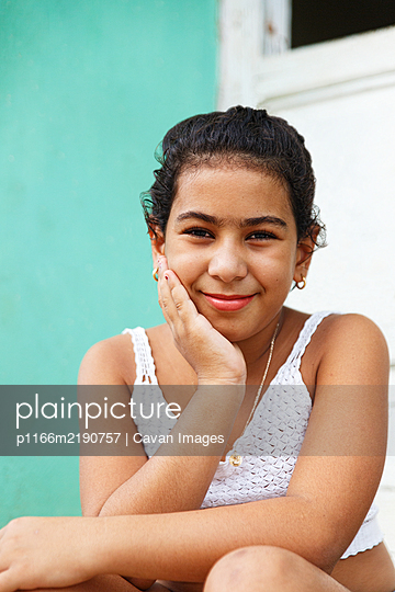 Cuban girl sitting in the doorway of her house, Trinidad-Cuba - p1166m2190757 by Cavan Images