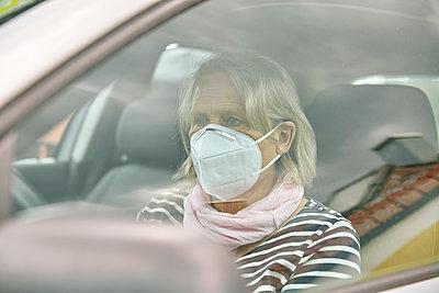 Seniorin mit Maske im Auto, Portrait - p1146m2187858 von Stephanie Uhlenbrock