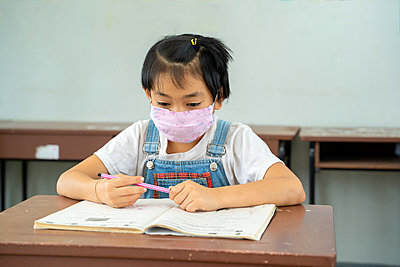 School kids wearing protective mask to Protect Against Covid-19 - p1166m2246774 by Cavan Images