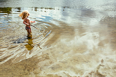 Little Girl Standing in Lake In Her Underwear with the Wind - p1238m1042087 by Amanda Voelker