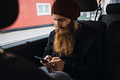 Bearded young man sitting on back seat of a car checking cell phone - p300m2060876 by Kike Arnaiz
