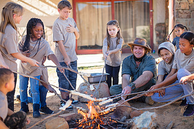 Children and guide roasting twist bread at camp fire - p300m2081550 by zerocreatives