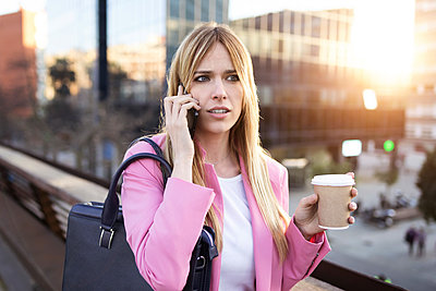 Young businesswoman using smartphone and holding coffee to go - p300m2114625 by Josep Suria