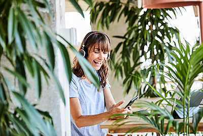 Cheerful woman with headphones using mobile phone wile sitting by table at home - p300m2220866 by Jo Kirchherr