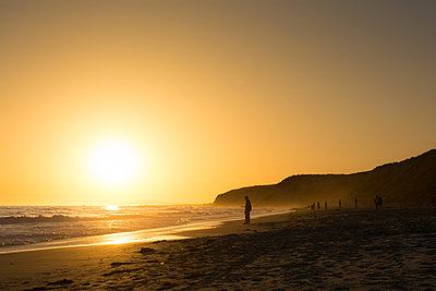 Backlit tourists on golden sunset beach,  Newport Beach, California, USA - p924m1494871 by John Manzoni