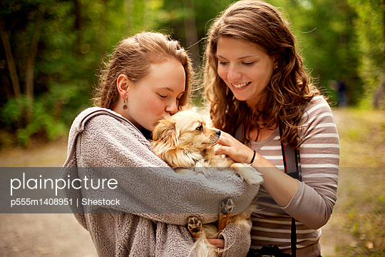 Girls petting puppy in forest - p555m1408951 by Shestock
