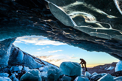 Side view of person climbing up on ice rock at the entrance to a glacial ice cave. - p1100m1520322 by Mint Images