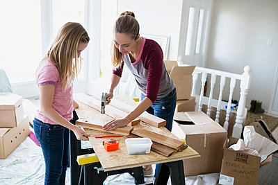 Daughter watching mother hammer nail into wood trim - p1192m1019844f by Hero Images